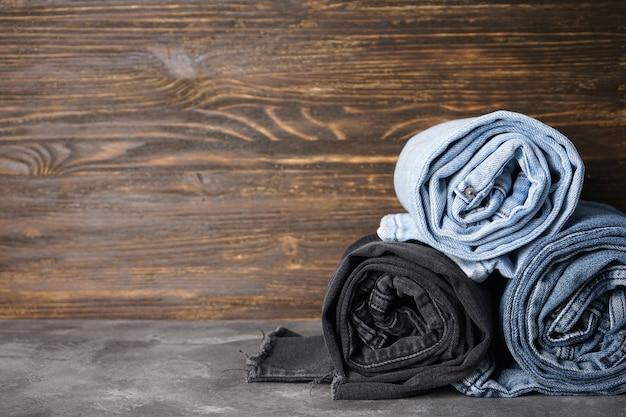 Jeans gevouwen op rollen op een houten achtergrond, plaats voor tekst.