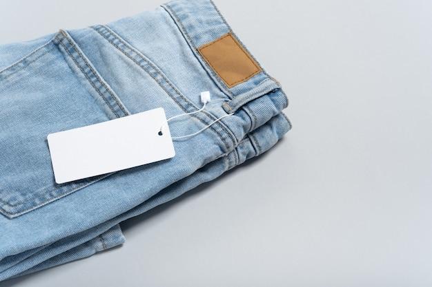 Jeans kleding witboek tag, blanco mockup labelsjabloon. grijze achtergrond, kopieer ruimte, plat leggen