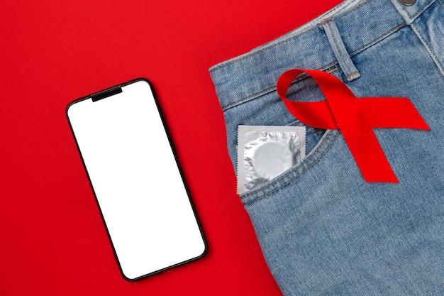 Jeans met condoom in de zak en een rood lint. plat leggen. bespotten. het concept van wereldaidsdag en veilige seks.