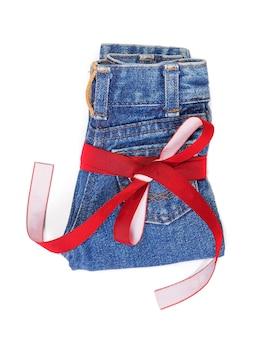 Jeans met decoratief lint. kleine schattige jeans vastgebonden met een rood lint