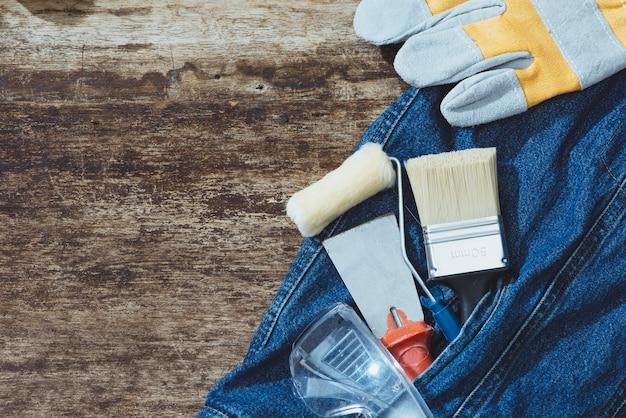 Jeans, reparatiemateriaal en veel handig gereedschap. bovenaanzicht met kopieerruimte