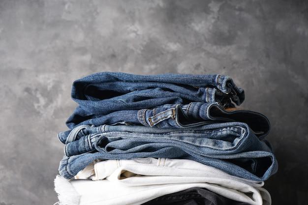 Jeans van verschillende kleuren. gevouwen jeans op grijze achtergrond,