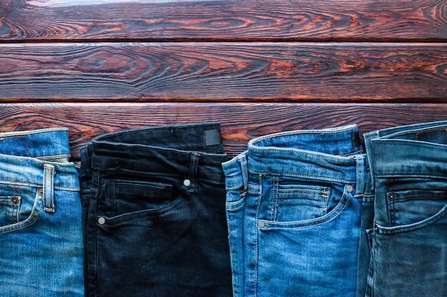 Jeans van verschillende kleuren op een houten achtergrond en ruimte voor tekst