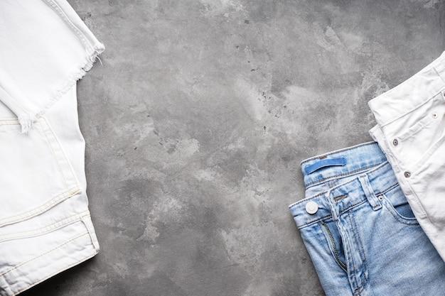 Jeans voor dames en spijkerbroeken over grijs, platliggend. plaats voor tekst.
