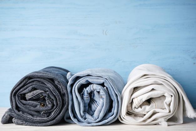 Jeans zijn gestapeld op een blauwe houten achtergrond, ruimte voor tekst. stapel jeans van verschillende tinten.