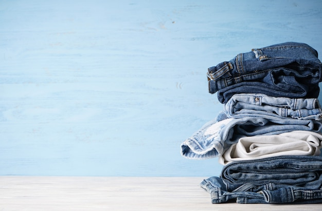 Jeans zijn gestapeld op een houten achtergrond met plaats voor tekst.