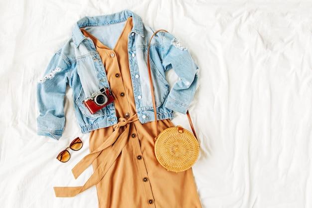 Jeansblauwe jas en beige jurk met bamboe tas op wit bed. stijlvolle herfstoutfit voor dames. trendy kleding. plat lag, bovenaanzicht.