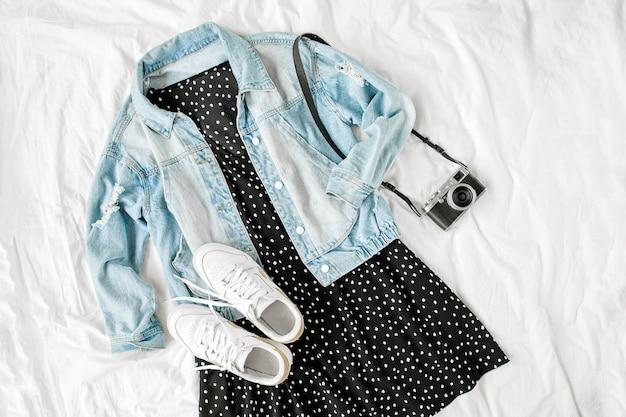 Jeansblauwe jas en zwarte jurk met retro fotocamera op wit bed. stijlvolle herfst- of lente-outfit voor dames. trendy kleding. plat lag, bovenaanzicht.