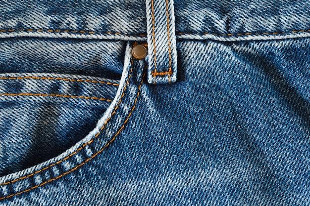 Jeansdenim, broekzakken aan de voorkant, naden met oranje draden, close-up macroweergave