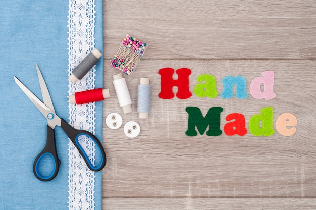 Jeansstof voor naaien, kant, accessoires voor handwerk en inscriptie handgemaakt van vilt op oude houten achtergrond. klosje garen, schaar, knopen, naaibenodigdheden.