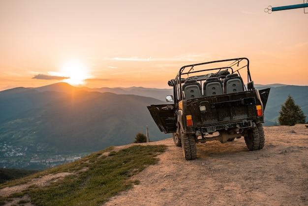 Jeepauto bij zonsondergang in het landschap van bergen