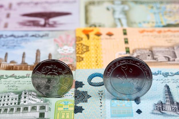 Jemenitische munten op de achtergrond van geld