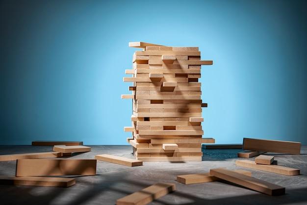 Jenga-spel, een toren van houten blokken op blauw