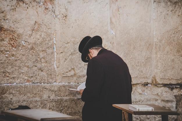 Jeruzalem, israel. 24 oktober 2018: othodoxe joodse man jammerend bij de westelijke muur, klaagmuur, een oude kalkstenen muur in de oude stad van jeruzalem, onderdeel van de uitbreiding van de tweede joodse tempel