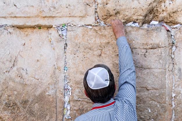 Jeruzalem israël, laat de brief achter met een gebed. tourist jood legt een brief met een verzoek aan god in de opening in de klaagmuur.