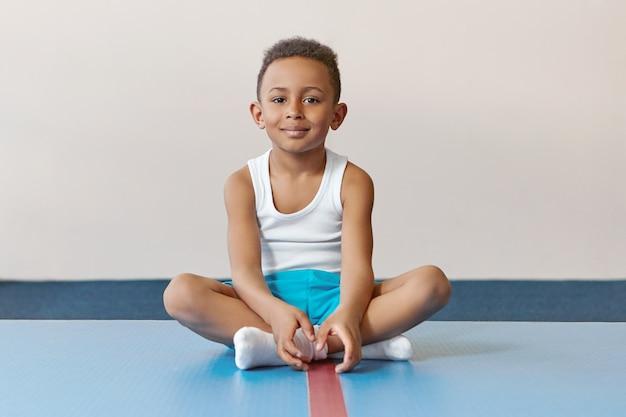 Jeugd, actieve levensstijl en gezondheidsconcept. knappe vrolijke afro-amerikaanse kleine jongen sokken dragen