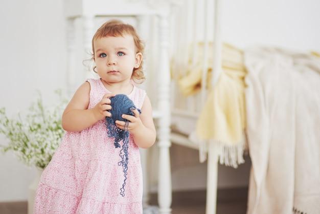 Jeugd concept. babymeisje in schattige jurk spelen met gekleurde draad. witte vintage kinderkamer