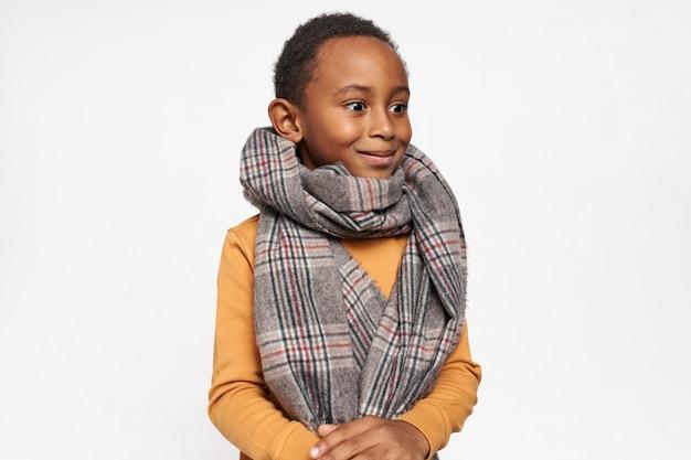 Jeugd concept. geïsoleerd portret van emotioneel verrast schattige zwarte jongen die warme sjaal draagt en glimlacht