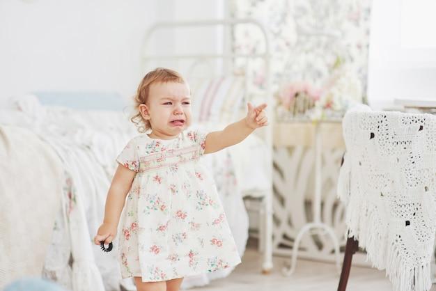 Jeugd concept. verdrietig en depressief meisje huilt in de kleuterschool. witte vintage kinderkamer