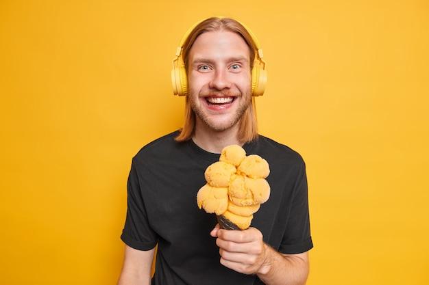 Jeugd en lifestyle concept. positieve roodharige hipster man houdt grote smakelijke ijs van mango smaak glimlacht gelukkig gekleed in casual zwart t-shirt luistert muziek via koptelefoon geïsoleerd op gele muur