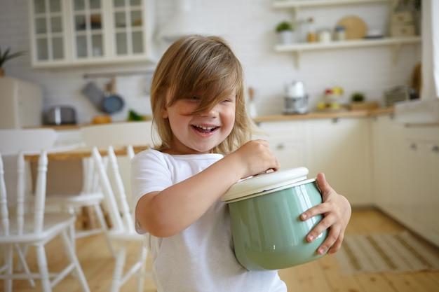 Jeugd en onschuld concept. mooie schattige babymeisje met charmante glimlach, spelen met moeders braadpan. leuke vrouwelijke steelpan van de kindholding, die soep voor diner gaat koken, gelukkig glimlachen
