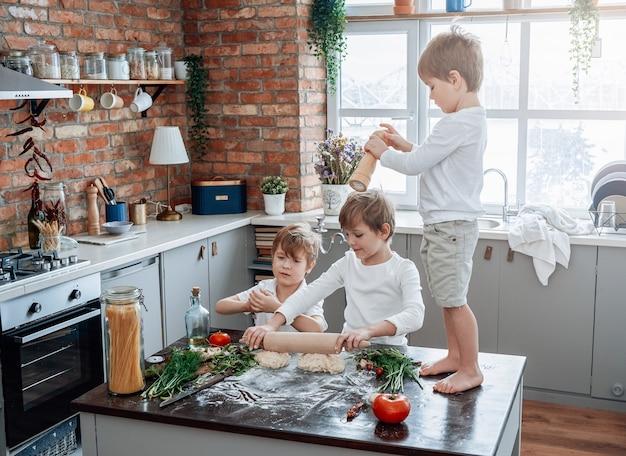 Jeugd en vrijetijdsbesteding thuis. drie peuterjongens spelen samen en leren overdag in de keuken te koken.