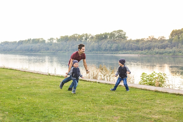 Jeugd familie concept vader speelt met twee zonen in de buurt van het meer
