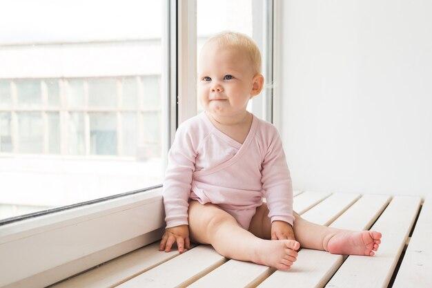 Jeugd, familie en zuigeling concept - babymeisje op de vensterbank thuis