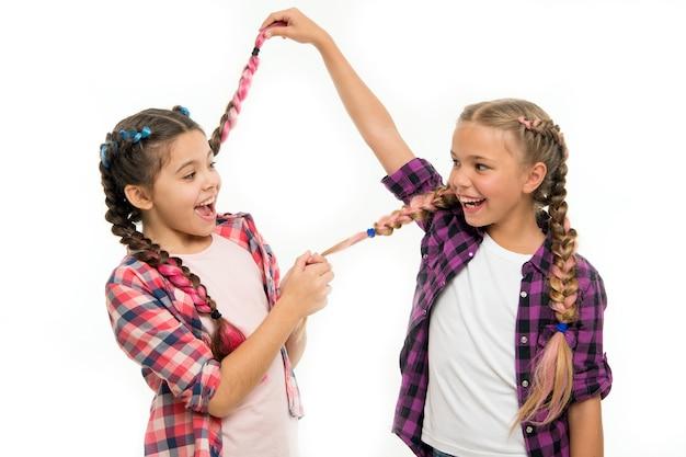 Jeugd geluk. vriendschap en zusterschap. gelukkige zusjes. schoonheid en mode. kleine kindermode. kinderdag. terug naar school. kleine meisjeskinderen met perfect haar. kijk hiernaar.