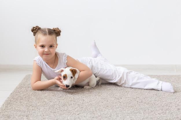 Jeugd huisdieren en honden concept klein kind meisje poseren op de vloer met puppy