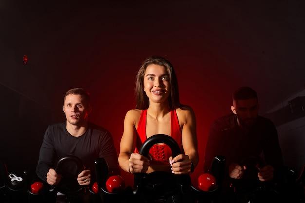 Jeugd in sportkleding, training fietsen in de sportschool, met de bedoeling van gezondheidszorg. blanke mannen en vrouwen schreeuwen om het lichaam gezond te maken met strakke spieren en het gewicht te verminderen