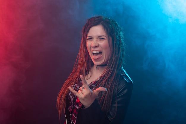 Jeugd, kapsel en modern concept - jonge vrouw die met dreadlocks over rood en blauw glimlachen
