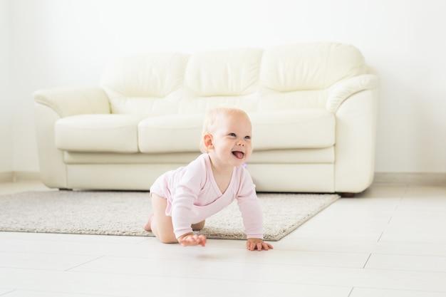 Jeugd, kinderen en babyhood concept - kruipende grappige babymeisje binnenshuis thuis