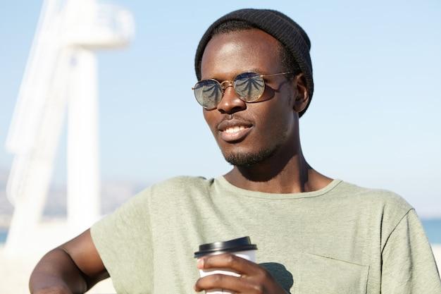 Jeugd, moderne levensstijl en geluk concept. aantrekkelijk trendy uitziende jonge afro-amerikaanse reiziger in zonnebril met spiegelglazen die op bank in toevluchtstad ontspannen, koffie hebben en zeelucht inademen