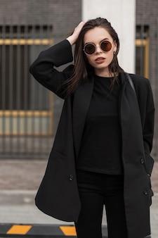 Jeugd nieuwe collectie elegante damesjassen. stijlvolle vrouw in vintage t-shirt in modieuze zwarte blazer buitenshuis. stedelijke zakelijke vrouwelijke uitloper