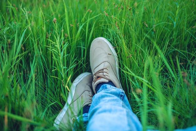 Jeugd sneakers op mannen benen in spijkerbroek op groen gras