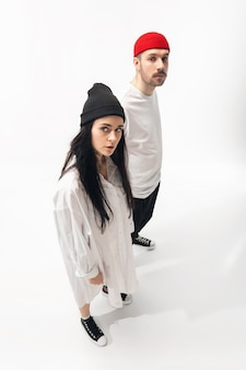 Jeugd. trendy modieus paar dat op witte studioachtergrond wordt geïsoleerd. blanke vrouw en man poseren in minimale stijlvolle kleding. concept van relaties, mode, schoonheid, liefde. copyspace.