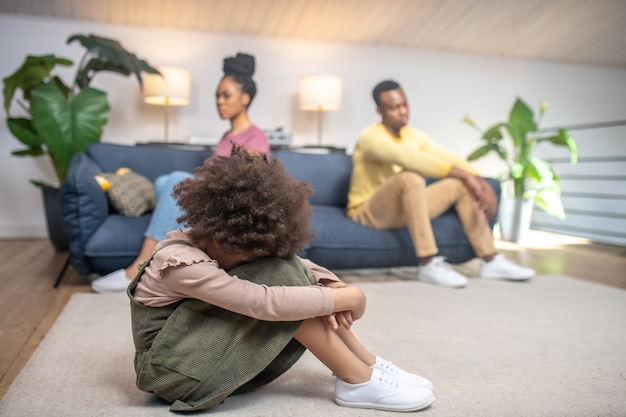 Jeugd verdriet. ongelukkig meisje met krullend haar zittend op de vloer met haar hoofd naar beneden en verdrietige ouders op de bank thuis sofa