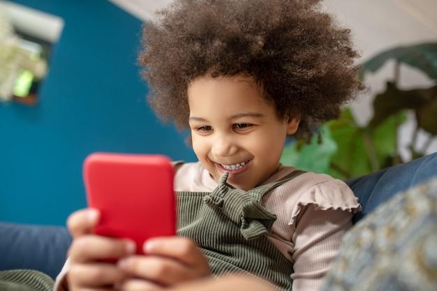 Jeugd, vreugde. vrolijk schattig klein meisje met een donkere huidskleur met donker krullend haar dat naar een rode smartphone kijkt die comfortabel thuis op de bank zit