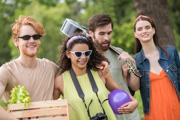Jeugd vrijetijdsbesteding. glimlachende jonge mensen in zonnebril met gitaar en doos met verse groenten wandelen knuffelen in de natuur op warme dag