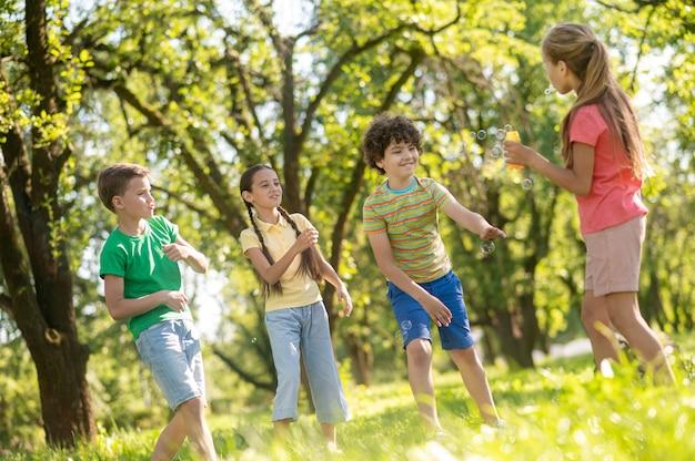 Jeugd. vrolijk lachende jongens en meisjes communiceren spelen met zeepbellen op groen gazon in park op zomerdag