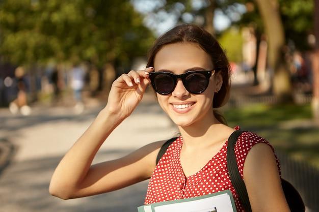 Jeugd, zomer, stijl en geluk concept. vrolijke modieuze mooi meisje met slank lichaam en schattige gelukkige glimlach hand in hand op haar zwarte zonnebril, leuke tijd buitenshuis doorbrengen, wandelen