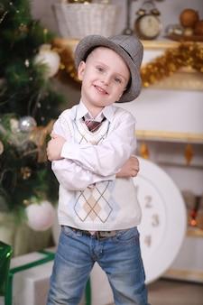 Jeugdherinneringen. kleine jongen in hoed kerstmis thuis vieren. jongenskind spelen in de buurt van kerstboom. vrolijk en helder kerstfeest. jeugdactiviteit en spel. vakantie met het gezin.