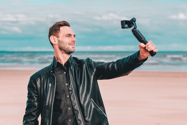 Jeugdige blogger die een selfie maakt of video streamt op het strand met behulp van een actiecamera met gimbal-camerastabilisator.