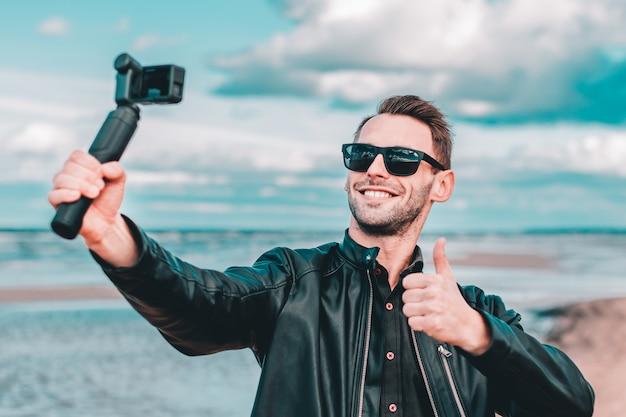 Jeugdige blogger in zonnebril selfie maken of video streamen op het strand met behulp van actiecamera met gimbal camera stabilizer.