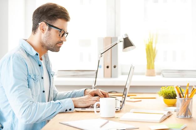 Jeugdige focus op geweldige oplossing. zijaanzicht van knappe jongeman in shirt en bril die op laptop werkt terwijl hij op zijn werkplek zit