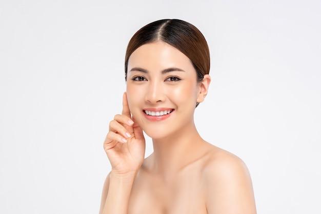 Jeugdige glimlachende vrij aziatische vrouw met hand wat betreft gezicht op witte achtergrond