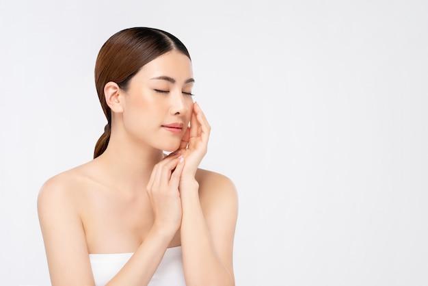 Jeugdige heldere huid aziatische vrouw met hand wat betreft gezicht en ogen het sluiten