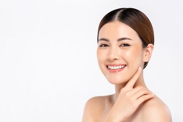 Jeugdige heldere huid die vrij aziatische vrouw met hand wat betreft gezicht glimlachen