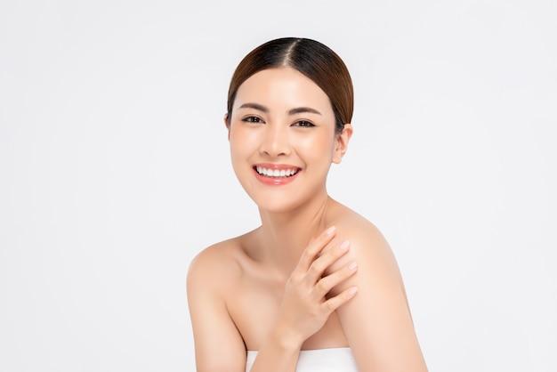 Jeugdige heldere huid die vrij aziatische vrouw voor schoonheidsconcepten glimlachen
